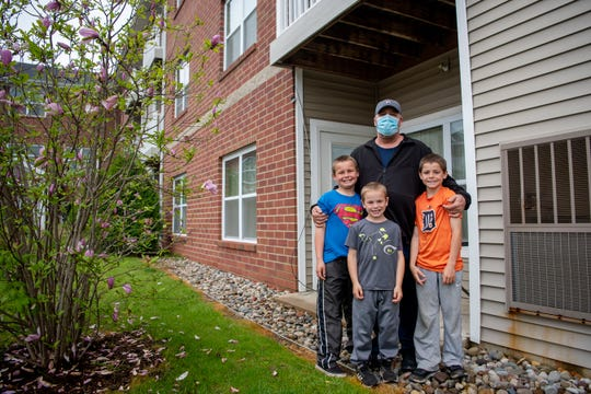 U.S. Army veteran John Sleight spends the day with his grandchildren Bo Miller, 9, Trentan Miller, 6, and Jaxsen Miller, 8, on Tuesday, May 19, 2020 in Battle Creek, Mich. Upon learning another resident in his building contracted COVID-19, Sleight is nervous to use apartment amenities, such as the laundry room.