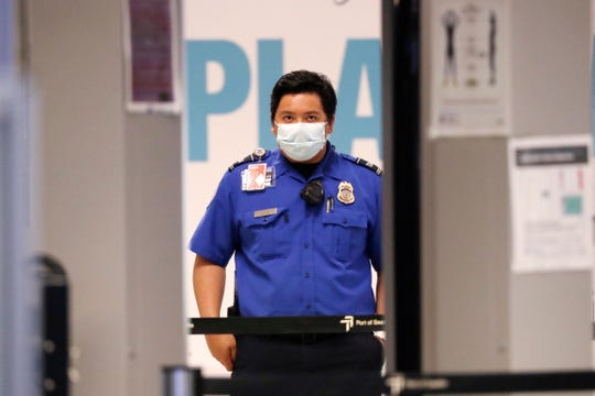 A TSA officer wears a protective mask while waiting to screen passengers at Seattle-Tacoma International Airport Monday, May 18, 2020, in SeaTac, Wash. Monday was the first day that travelers at the airport were required to wear face coverings in the public areas there. The Port of Seattle has encouraged its employees to wear face coverings, and all federal agencies that operate at the airport require their employees to wear face coverings. All airlines operating at SeaTac require employees and passengers to wear face coverings. (AP Photo/Elaine Thompson)