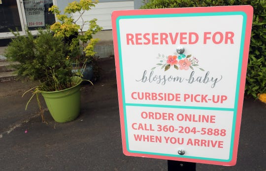 The curbside pick-up sign in the parking lot of Blossom Baby in Silverdale on Tuesday, May 19, 2020.
