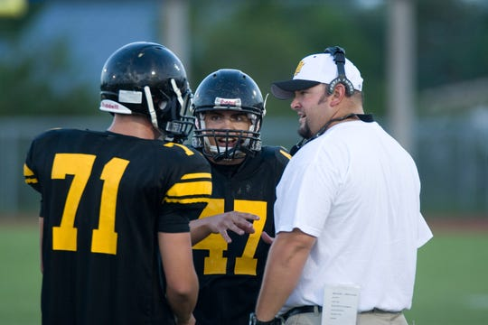 Merritt Island assistant coach Matt Martin discusses strategy with Ryan Adair (71) and Tyler Murray (47) during a timeout in 2008.