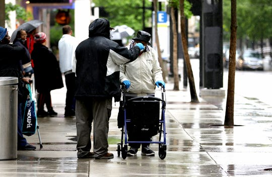 A man adjusts a woman's face mask as they wait in the rain for a bus at Government Square Downtown Tuesday morning. The chance for showers will continue Tuesday night into Wednesday, with the greatest chance for shower activity will be near the Ohio River, the National Weather Service said. Photo shot Tuesday May 19, 2020.