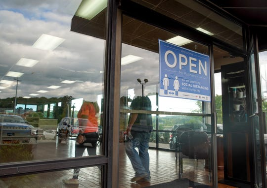 Customers enter the front door where a sign greeting them advises social distancing at Gary Matthews Motors in Clarksville, Tenn., on Monday, May 18, 2020.