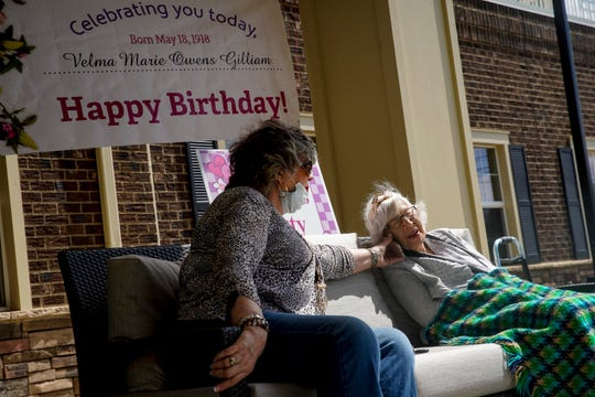 Shirley Ross holds a phone for her mother, Velma Gilliam, to talk to family before the start of a drive-by parade celebrating Gilliam's 102nd birthday at Jubilee House in Clarksville, Tenn., on Monday, May 18, 2020.