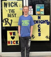 Nick Franks stands outside Keene Elementary School where signs have been posted to support him. Staff and students also drove by his home at the end of April to support him as he battles cancer.