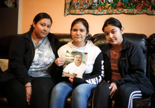 Maria Andrade of Marshalltown holds a photo of her father, Jose Andrade-Garcia, joined by her sister, Alejandra, 17, left, and Andrade-Garcia's granddaughter Diana, 15, at Andrade-Garcia's home on Tuesday, May 19, 2020, in Marshalltown. Andrade-Garcia passed away after a monthlong battle with COVID-19.