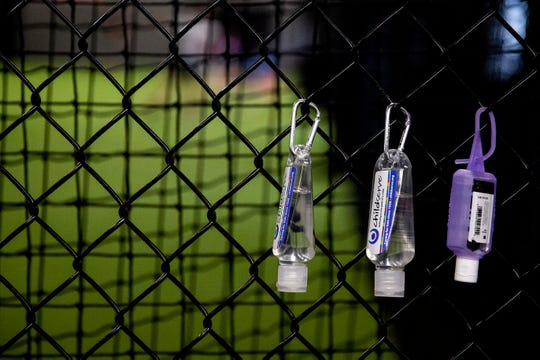 Containers of hand sanitizer hang on the fence just inside the door of Dugout Sports on Tuesday, May 19, 2020, in Fairfax. Professional baseball players from eastern Iowa have been working out here to stay in shape while the baseball season is on hold because of COVID-19.