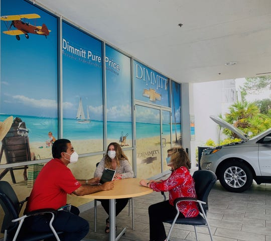 Dimmitt Chevrolet sales associate Raheel Syeld reviews the features on a new Chevrolet Equinox SUV with two customers in an outdoor office area during the coronavirus pandemic.