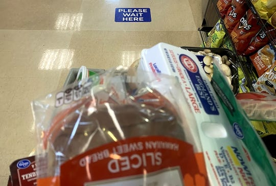A sign on the floor marks the area where the next person in line waits for a cashier at a Kroger store in east Detroit. The signs are spaced at 6 feet apart to comply with social distancing guidelines.