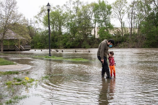 Adam Chase and his son Oliver Chase, 5, both of Ypsilanti, walk on the flooded sidewalk with their rainbows at the Riverside Park in Ypsilanti, Tuesday, May 19, 2020.