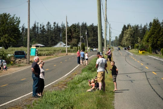 U.S. residents, left, and Canadian residents, right, gather across a ditch along the Canada-U.S. border, in Abbotsford, British Columbia, Sunday, May 10, 2020. The stretch of international border southeast of Vancouver has become a popular meeting spot for families, loved ones and friends separated due to the closure of the Canada-U.S. border to non-essential travel due to the coronavirus concerns. (Darryl Dyck/The Canadian Press via AP)