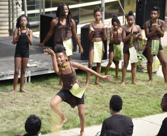 Maya Driscoll, 12, a member of the Alnur African dance troupe, performs at the African World Festival at the Charles H. Wright Museum of African American History, Aug. 19, 2018, Detroit.