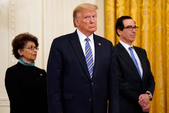 In this April 28, 2020 file photo President Donald Trump, along with Jovita Carranza, administrator of the Small Business Administration, and Treasury Secretary Steven Mnuchin listen during an event about the Paycheck Protection Program used to support small businesses during the coronavirus outbreak, in the East Room of the White House in Washington.