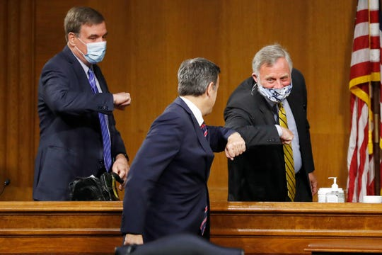 Rep. John Ratcliffe, R-Texas, center, arrives to a Senate Intelligence Committee nomination hearing on Capitol Hill in Washington, Tuesday, May. 5, 2020 and is greeted by committee Chairman Sen. Richard Burr, R-N.C. and Vice Chairman Sen. Mark Warner, D-Va., left.