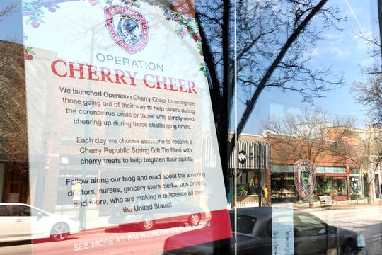In this May 2, 2020 photo, a nearly deserted Front Street is reflected in the window of Cherry Republic, a popular downtown store that sells products made with the region's signature fruit in Traverse City, Mich.