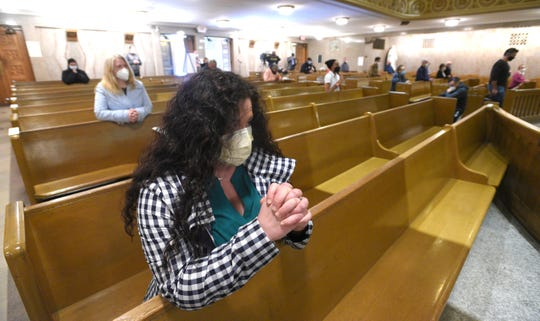 Andrea Rossi, of Farmington Hills, prays before communion. Approximately 35 worshippers attend one of the first public daily masses at St. Aloysius Catholic Church in downtown Detroit, Tuesday afternoon, May 19, 2020, since the state lockdown from COVID-19, as Father Mario Amore conducts the mass.