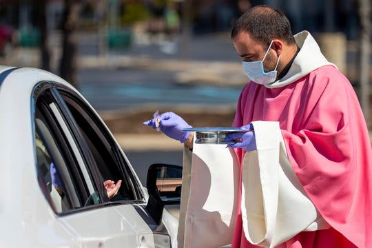 In this Sunday, March 22, 2020 file photo, the Rev. William A. Mentz, pastor of the Scranton, Pa.-based St. Francis and Clare Progressive Catholic Church, wears a mask and gloves while distributing prepackaged communion to the faithful attending Mass while sitting in their cars in the parking lot of a shopping center in Moosic, Pa.
