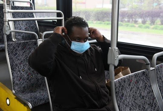 Raymoan Autrey, 48, of Detroit puts on the mask given to him by the bus driver before he got on the 17 bus in Detroit on May 18, 2020. To protect the health and safety of our customers and employees, DDOT is temporarily suspending fare collection for all trips and requesting that customers limit non-essential bus travel until further notice.