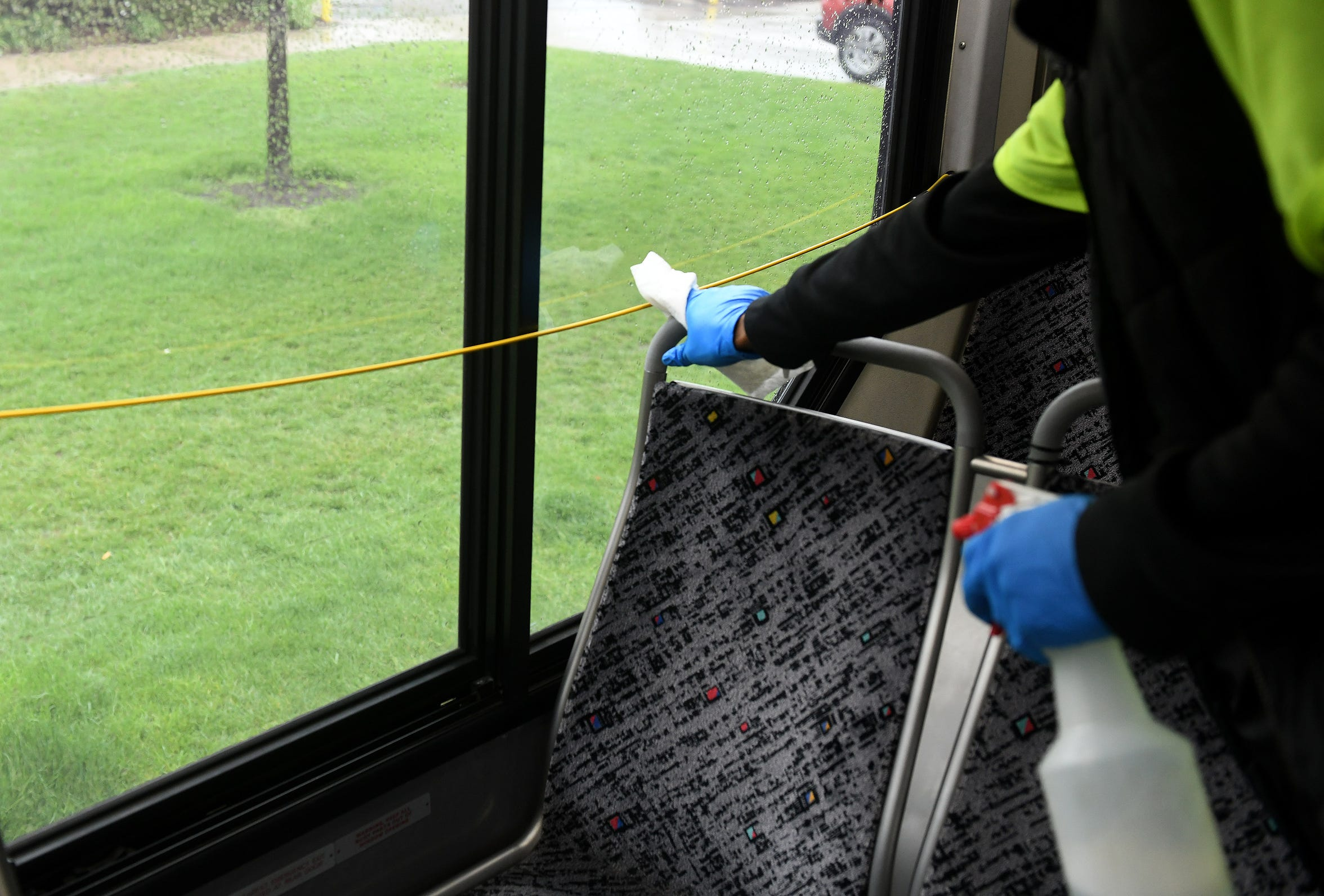 An employee who did not want to be identified disinfects the 17 bus during the stop at Ascension St. John Hospital in Detroit on May 18, 2020. This is the halfway point of the eastbound loop from the State Fair Transit Center and sits there for approximately 30 minutes.