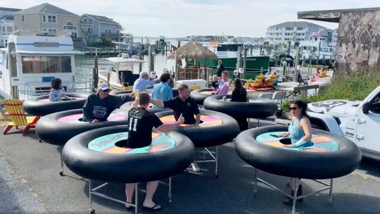 """In this image made from video, """"bumper tables,"""" created by the company and designed to allow people to practice social distancing while eating and talking, are debuted at Fish Tales, a restaurant in Ocean City, Md."""