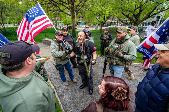 Phil Robinson, center, of Michigan Liberty Militia, greets members from other militias that also provided security for the event.