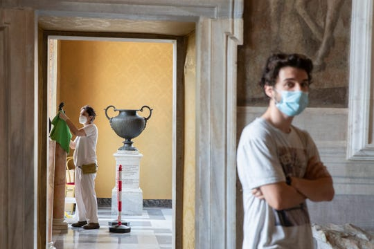 A museum employee cleans a statue, as a visitor wearing face mask to prevent the spread of COVID-19 walks in the Rome's Capitoline Museums, Tuesday.