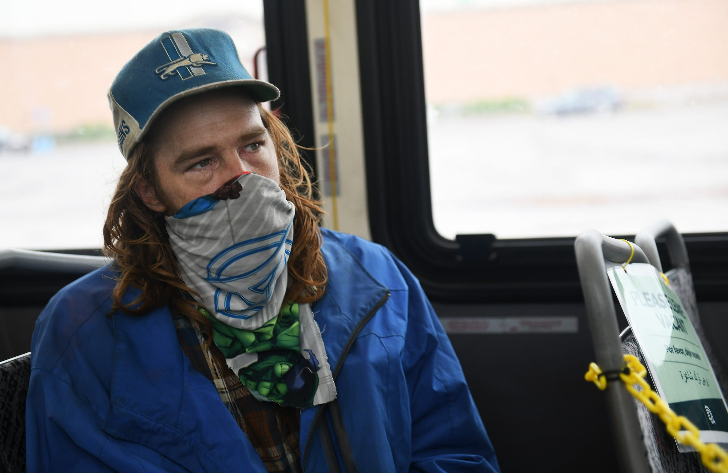 William McLoven, 35, of Detroit talks about riding the DDOT bus in Detroit on May 18, 2020. McLoven, who says he is homeless and squats in an empty home, made his mask from a bedsheet and says he makes one every few days.