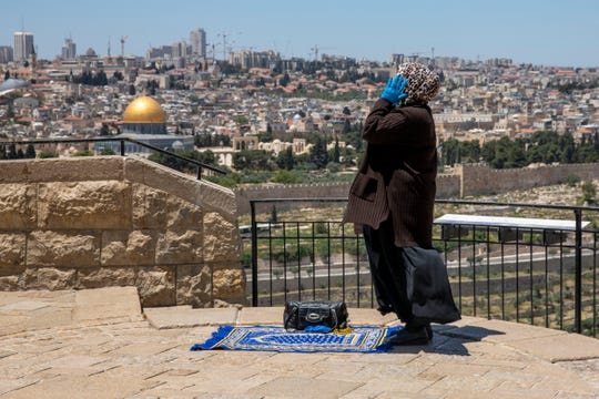 A Muslim woman wears gloves prays in east Jerusalem's Mount of Olives, overlooking the Dome of the Rock and al-Aqsa mosque compound, which remains shut to prevent the spread of coronavirus during the holy month of Ramadan, Friday, May 1, 2020.