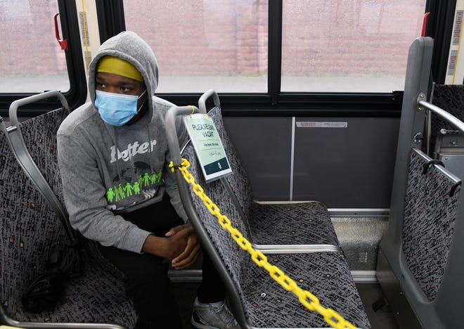 Andre Morris, 17, of Harper Woods rides on bus 17  in Detroit on May 18, 2020. To protect the health and safety of our customers and employees, DDOT is temporarily suspending fare collection for all trips and requesting that customers limit non-essential bus travel until further notice.