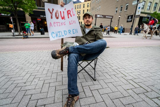 "Jon Lown, 28, of Grand Rapids, attends the ""American Patriot Rally — Sheriffs Speak Out"" event at Rosa Parks Circle in Grand Rapids, May 18, 2020. Lown ""doesn't see the need to protest"" and wants people to ""stay home so we can all go back to our normal lives."""