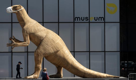 A boy walks by a model of a dinosaur wearing a face mask, during a partial lockdown to prevent the spread of the coronavirus, at the Museum of Natural History in Brussels, Tuesday.