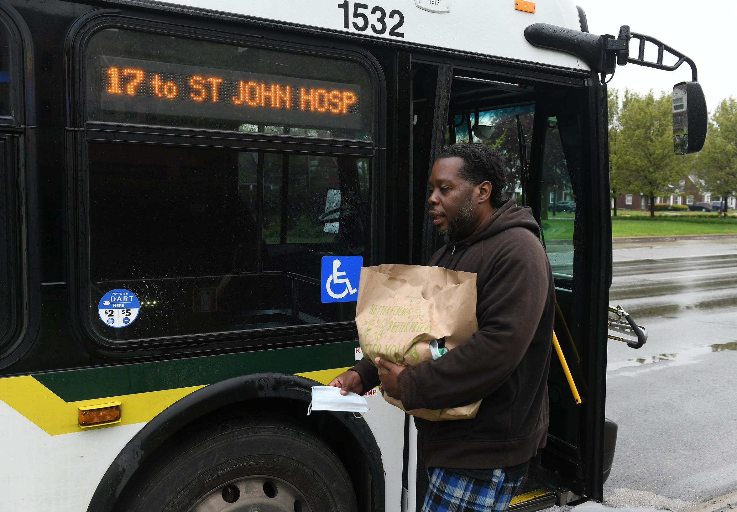 Raymoan Autrey, 48, of Detroit takes the mask given to him by the bus driver before he enters the 17 bus in Detroit on May 18, 2020. To protect the health and safety of its customers and employees, DDOT is temporarily suspending fare collection for all trips and requesting that customers limit non-essential bus travel until further notice.