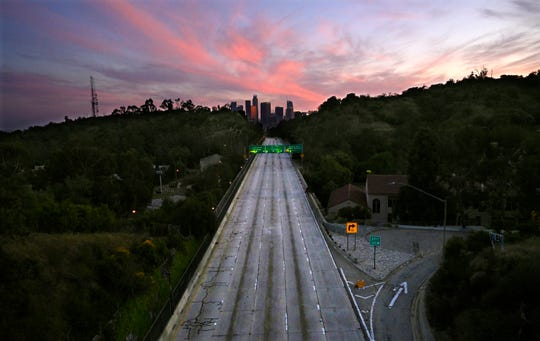 FILE - In this April 26, 2020, file photo, empty lanes of the 110 Arroyo Seco Parkway that leads to downtown Los Angeles is seen during the coronavirus outbreak in Los Angeles.