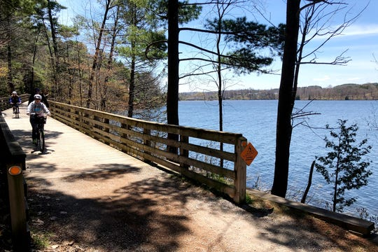 In this Saturday, May 16, 2020 photo, bicyclists cruise along the Boardman Lake Trail in Traverse City, Michigan on The trail is among many popular outdoor recreation spots in the area, where the tourism industry has suffered because of stay-at-home orders resulting from the coronavirus.