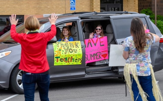 """Holding signs Ashlyn Sexton, 12-years-old, with her family wave to teachers and staff at Holy Redeemer School hold a """"Goodbye Parade"""" with a Luau theme for their students Tuesday, May 19, 2020."""