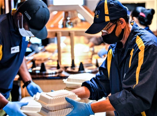MWR personnel prepare food containers in support of aircraft carrier USS Theodore Roosevelt.
