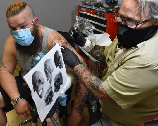 "Artist David ""Doc"" Bentley, right, works on a tattoo that Jeff Poarch, left, began with Bentley before the coronavirus outbreak. Bentley's Bentley Tattoo Company in Byram, Miss., reopened on Monday, after Governor Tate Reeves lifted additional non-essential business restrictions. Tuesday, May 19, 2020"