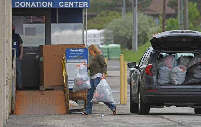 A woman unloads a car full of donations to the Goodwill Store in Ontario on Tuesday.