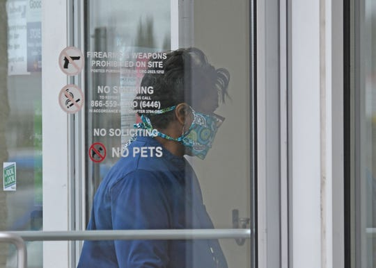 A shopper enters the Goodwill store on Tuesday morning wearing a mask.