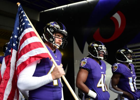 Baltimore Ravens long snapper Morgan Cox (46) walks out with a flag prior to the game against the Houston Texans at M&T Bank Stadium.