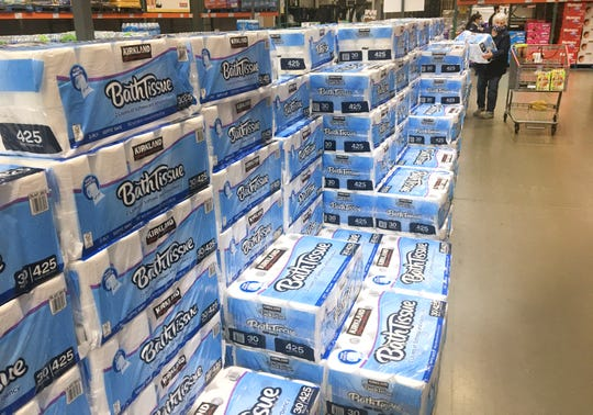 A woman places a 30-roll package of toilet paper from a large stack in her cart Mondayat Costco in Menomonee Falls. Retail toilet paper demand swelled to unforeseen heights in March, with $1.45 billion in toilet paper sales in the four-week period ending March 29, up 112% from a year earlier, according to IRI, a Chicago-based market research firm. Retail stores couldn't keep enough supply on the shelves, and the supply chain became strained by the demand.
