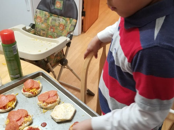 As a result of the pandemic, Milwaukee mom Kimberly Diaz has had more time to cook with her kids. Here, her daughter, Alayna, makes her own pizza.