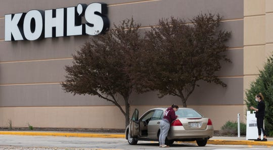 A store associate delivers a purchase to a drive-up customer Tuesday at the Kohl's store in Fond du Lac. The coronavirus and store closures cut Kohl's Corp. sales by 43.5% in the first three months of 2020 compared to the same period last year.  Kohl's reported that its net sales in the first quarter of 2020 were $2.16 billion, down from around $3.8 billion during the same time in 2019.     MARK HOFFMAN/MILWAUKEE JOURNAL SENTINEL