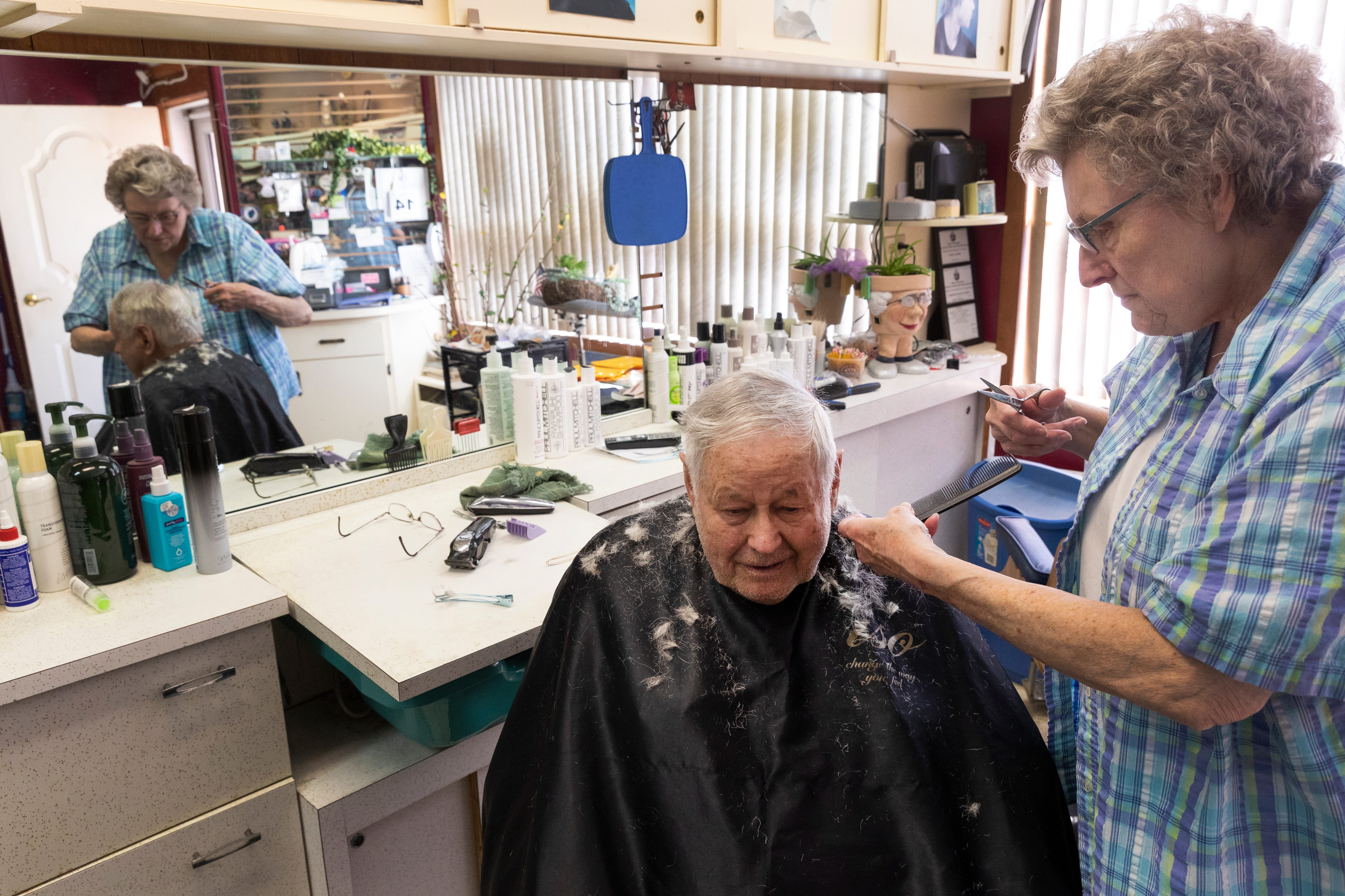 Carol Hubing gives longtime customer Franz Grossenbacher a haircut at her salon in Loyal on May 15. Grossenbacher was one of her first customers since the Wisconsin Supreme Court overruled business restrictions put into place by Gov. Tony Evers. Clark County has a population of about 35,000 people and about 166,000 dairy cattle.