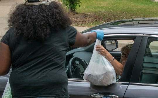 A Cahawba House employee gives curbside service to a customer on Monday, May 18, 2020, in Montgomery.