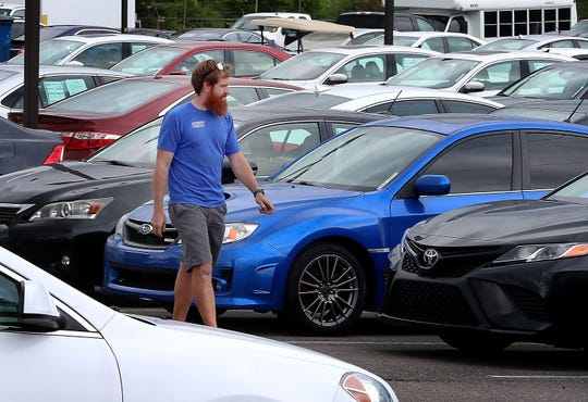 Erik Bennett of Automotive Cosmetics, a contract worker for City Auto, walks across the sales lot at City Auto of Murfreesboro, on Tuesday, May 19, 2020.