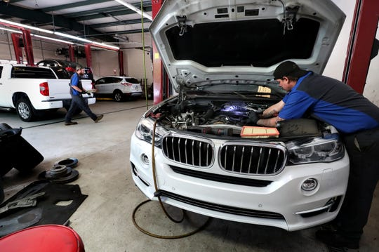 Ian Wells, a service department technician at City Auto of Murfreesboro, works on a vehicle on Tuesday, May 19, 2020, at the dealership, as service technician Austin Wood walks to another vehicle.