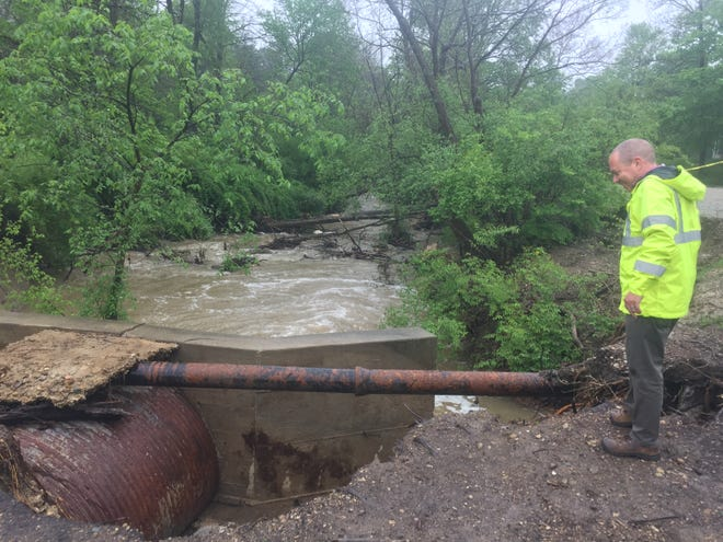 Granville Village Manager Herb Koehler examines previous damage to the bridge into Denison Golf Club caused by flooding earlier this year. Koehler was checking conditions Thursday afternoon with steady rain fallin and Raccoon Creek rising.