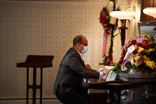 Funeral for Dominick Brancaccio at Patrick J. Conte Funeral Home in Elmwood Park on Tuesday, May 19, 2020. Frank Baez, a foster son of Brancaccio, kneels at the casket.