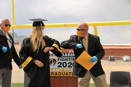 Alamogordo High School Senior Flora Jarvis elbow bumps Alamogordo Public Schools Superintendent Jerrett Perry at the AHS 2020 Graduation.  Due to COVID-19 coronavirus restrictions,  AHS held a socially distanced graduation ceremony.