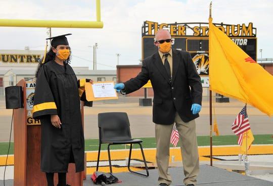 Alamogordo High School  senior Adriana Jimenez receives her diploma at the AHS 2020 Graduation May 19, 2020.  Due to COVID-19 coronavirus restrictions,  AHS held a socially distanced graduation ceremony.